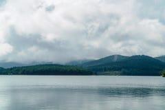 Montanhas verdes e nebulosas com lago Fotos de Stock