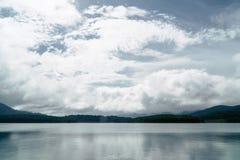 Montanhas verdes e nebulosas com lago Fotografia de Stock Royalty Free