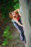 Montanhista bonito da mulher que escala a rocha íngreme com corda fotografia de stock royalty free
