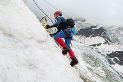 Montanhista com machados de gelo Fotos de Stock Royalty Free