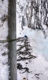 Montanhista de gelo masculino em um casaco azul a rappelling de uns trilhos da ponte em uma cachoeira congelada vertical fotos de stock royalty free