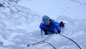 Montanhista de gelo masculino em um casaco azul em uma cachoeira congelada íngreme no inverno profundo nos cumes de Suíça foto de stock royalty free