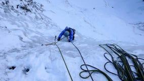 Montanhista de gelo masculino em um casaco azul em uma cachoeira congelada íngreme no inverno profundo nos cumes de Suíça imagem de stock