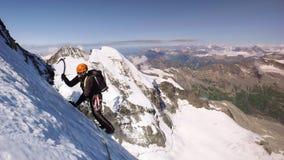 Montanhista de montanha masculino em uma geleira alpina alta com uma grande ideia da paisagem fantástica da montanha atrás dele fotos de stock
