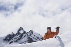 Montanhista de montanha que alcança sobre o pico nevado Foto de Stock