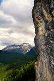 Montanhista de rocha aventuroso na cara vertical alta da rocha nos cumes, Itália fotos de stock