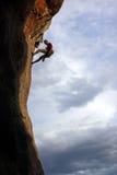 Montanhista de rocha de encontro ao fundo do céu nebuloso Fotografia de Stock Royalty Free
