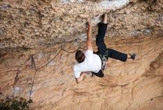 Montanhista de rocha em sua maneira desafiante acima Fotografia de Stock Royalty Free