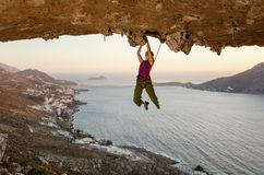 Montanhista de rocha fêmea na rota de desafio na caverna no por do sol imagem de stock