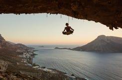 Montanhista de rocha fêmea novo que pendura na corda na posição do asana fotos de stock royalty free