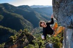Montanhista de rocha feliz que ascensão um penhasco desafiante Esporte extremo c fotografia de stock