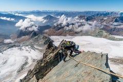 Montanhista de rocha no cume em Grossglockner, a montanha a mais alta de Studlgrat em Áustria fotos de stock