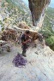 Montanhista de rocha que enrola uma corda após a subida Fotografia de Stock Royalty Free