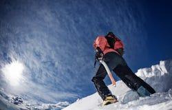 Montanhista em um cume nevado imagens de stock