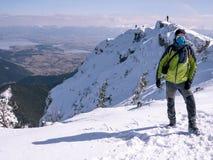 Montanhista experiente na parte superior de montanhas do inverno imagem de stock