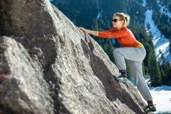 Montanhista fêmea novo sobre um pedregulho natural fora imagem de stock