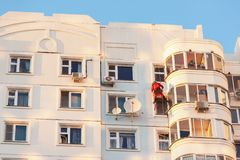 Montanhista industrial fixado nas cordas da segurança que puttying e que pintam a fachada da construção no dia ensolarado Vist fotografia de stock