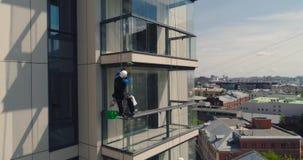 Montanhista industrial - limpeza da fachada Zangão do ar da fotografia aérea filme