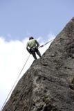 Montanhista que escala em uma rocha Foto de Stock