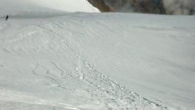Montanhista que move pela inclinação de montanha nevado subida na montagem de Kazbek no dia ventoso ensolarado vídeos de arquivo