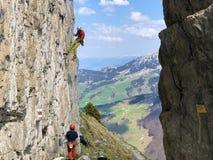 Montanhistas alpinos nos penhascos da montanha de Ebenalp na regi?o de Appenzellerland e na cordilheira de Alpstein imagem de stock royalty free