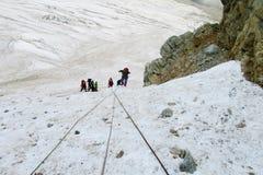 Montanhistas de montanha com cordas na neve Fotografia de Stock