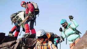 Montanhistas no equipamento lentamente para baixo um após o outro da rocha, ajudando-se são vestidos com especial filme
