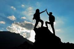 Montanhistas no sucesso da silhueta dos target&climbers Fotografia de Stock Royalty Free