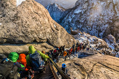 Montanhistas que atravessam uma inclinação íngreme coberta com a neve Imagem de Stock