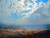 Sunlight between the earth and sky. Montanious landscape with cloudy sky and scattered breezes accompanied by sunrays in a shot of height, gopro shot Stock Image