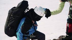 Montant la pente raide au coup de main de grimpeur et aidant à s'élever  teamwork banque de vidéos