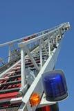 Montante da escada e sirene azul do caminhão dos sapadores-bombeiros durante uma emergência Fotografia de Stock