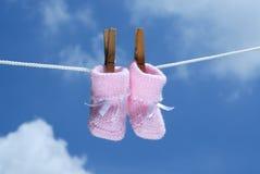 Montantes cor-de-rosa do bebê que haning em uma linha de roupa Fotografia de Stock