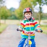 Montar a caballo activo lindo del niño pequeño en la bici Fotos de archivo libres de regalías