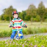 Montar a caballo activo lindo del niño pequeño en la bici Imágenes de archivo libres de regalías