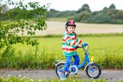 Montar a caballo activo lindo del niño pequeño en la bici Fotografía de archivo libre de regalías