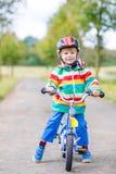 Montar a caballo activo lindo del niño pequeño en la bici Fotos de archivo