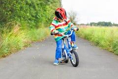 Montar a caballo activo lindo del niño pequeño en la bici Imagen de archivo libre de regalías