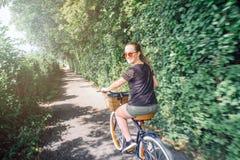 Montar a caballo adolescente feliz de la muchacha en la bicicleta en el día soleado Imágenes de archivo libres de regalías