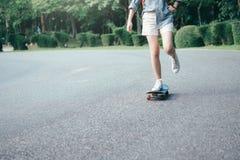 Montar a caballo adolescente joven de la muchacha de la ANSA en longboard en el camino Fotos de archivo