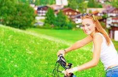 Montar a caballo adolescente juguetón de la muchacha en la bicicleta Imagen de archivo