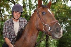 Montar a caballo adolescente un caballo Fotografía de archivo libre de regalías