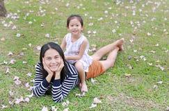 Montar a caballo alegre de la niña en la parte posterior su mamá que miente en campo verde con completamente la flor del rosa de  fotos de archivo libres de regalías