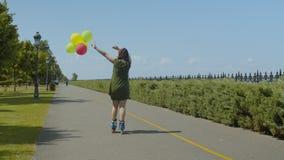 Montar a caballo alegre del rodillo de la mujer con los globos al aire libre metrajes