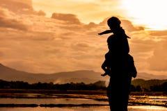 Montar a caballo asiático de la niña de la silueta en el father& x27; hombro de s Fotografía de archivo libre de regalías