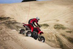 Montar a caballo ATV del adolescente en dunas de arena Imagen de archivo libre de regalías
