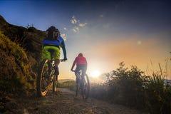 Montar a caballo biking de las mujeres y del hombre de la montaña en las bicis en la montaña de la puesta del sol fotos de archivo