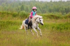 Montar a caballo confiado del pequeño bebé un caballo en un galope a través del campo Fotografía de archivo