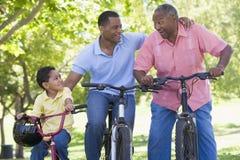 Montar a caballo de abuelo de la bici del nieto y del hijo Imagenes de archivo