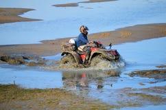 Montar a caballo de ATV en fango y agua Foto de archivo libre de regalías